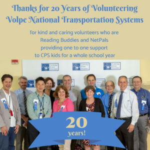 Eleven people Some wearing ties and some wearing blue ribbons, men and women iwth thanks for 20 years of volunteering Volpe National Transportation Systems