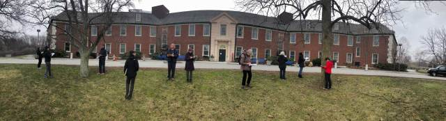 Ten people in jackets are drawing on sketchbooks in front of a very wide, imposing two story brick building, standing on barely green grass on a blustery day amidst several 4-foot-diameter still-leafless trees.