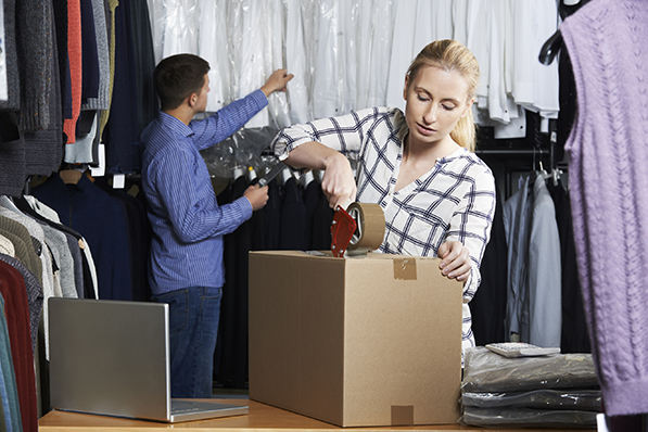 Couple Running Online Clothing Store Packing Goods For Dispatch
