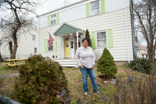 Photo of CFHC Client Mavis Silvera. She is standing in front of her home - a white house with green shutters - and smiling.