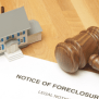 "Image description: Miniature house sits on table on top of paperwork reading ""Notice of Foreclosure,"" with gavel on top of paperwork."