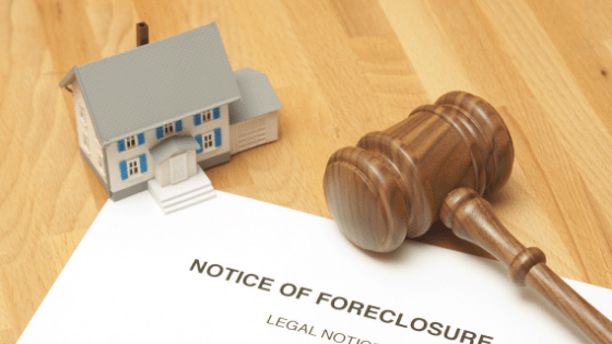 """Image description: Miniature house sits on table on top of paperwork reading """"Notice of Foreclosure,"""" with gavel on top of paperwork."""