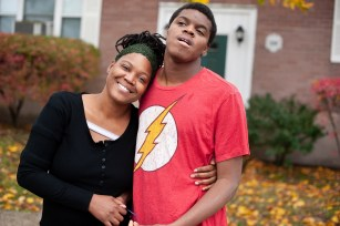 A mother and her teen son stand in front of their apartment building with arms around each other.