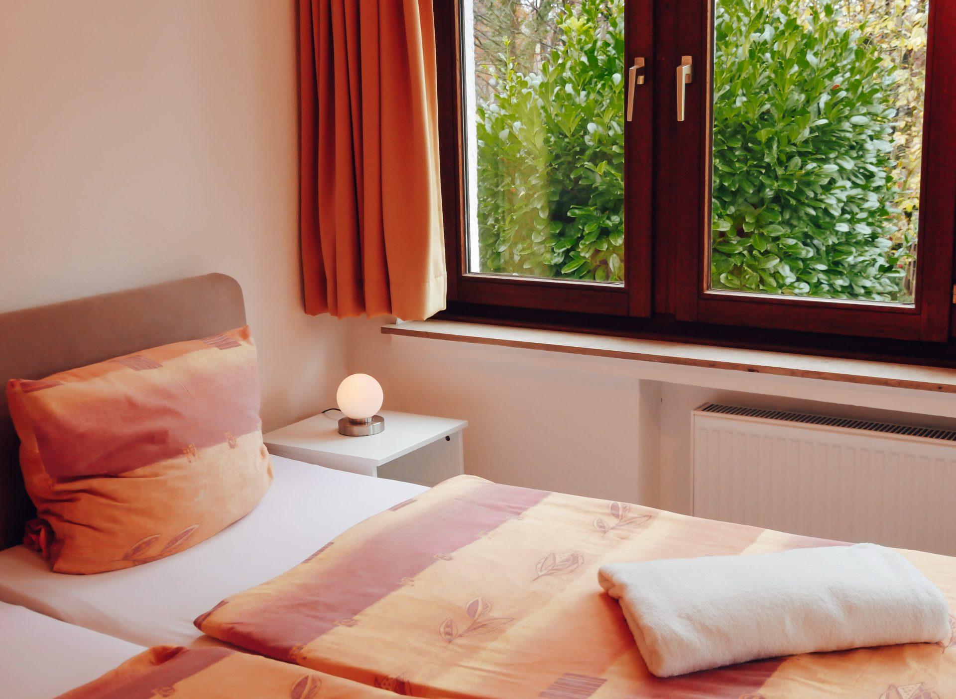 Zimmer in Lindlar » Bellevue im Bergischen Land » frisch bezogenes Bett mit bunter Bettwäsche