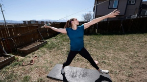 FILE - In this April 29, 2020, file photo, Olympic javelin thrower Kara Winger uses a cable system to simulate throwing a javelin as she trains outside her home in Colorado Springs, Colo. (AP Photo/David Zalubowski, File)
