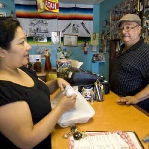 Arturo Zendeja speaks with a customer at his restaurant in July at his restaurant, El Taco Tako, 202 S. Chestnut St., Arcola, Ill. Zendeja and his wife, Maria, moved to Arcola 12 years ago. Arturo is a native of Cadereyta Jimenez in Mexico. They are part of a growing Latino population in the area, which is known for its broomcorn.