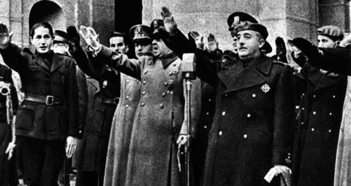 Dionisio Ridruejo (a la izquierda), miembro de Falange, realiza el saludo fascista junto a Franco ante la tumba de José Antonio Primo de Rivera.
