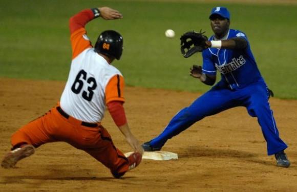 Jugada en primera base de Juniet Flores, del equipo Naranja. Foto: Marcelino Vázquez / AIN