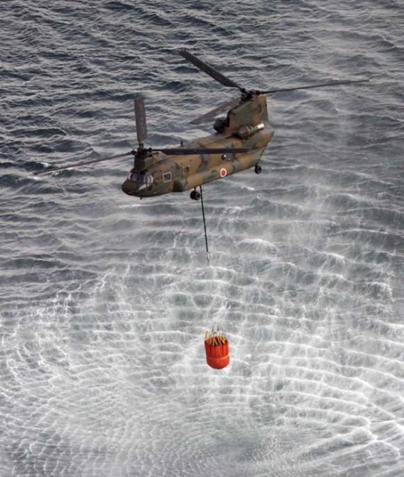 El Helicóptero de la Fuerza Aérea de Japón recoge agua de mar para verter sobre sobre el reactor de Fukushima. Foto: AFP