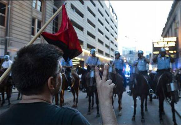 Un manifestante hace con sus dedos la señal de la victoria mientras protesta contra la cumbre de la OTAN en una calle de Chicago (EEUU). EFE/TANNEN MAURY