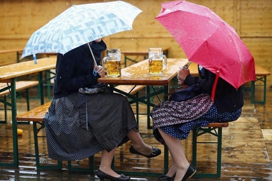 Dos mujeres toman cerveza bajo la lluvia durante la Oktoberfest, el festival de cerveza más grande del mundo