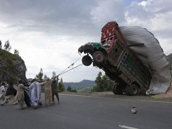 Unos optimistas se esfuerzan por halar un camión sobrecargado que volcó en Paquistán. Foto: REUTERS/Mian Khursheed.