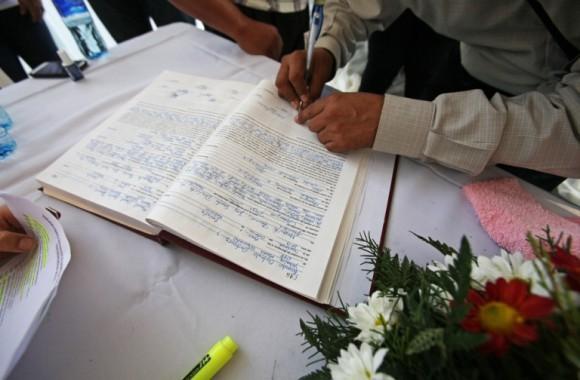 Un hombre firma en un libro en una maratón de bodas masivas en Managua. Foto: Mario Lopez / EFE