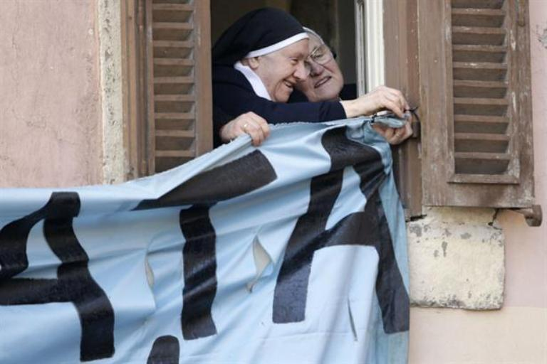 Monjas emocionadas cuelgan un cartel para que el Papa lo vea. Foto AP