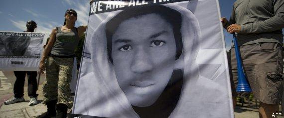 Dos manifestantes sujetan una pancarta con el rostro de Trayvon Martin en Los Ángeles. Foto: AFP.