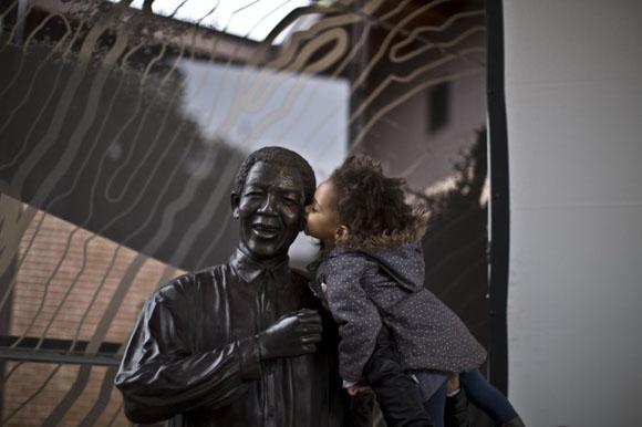 Una niña sudafricana besa la estatua del presidente Nelson Mandela en Johannesburgo (Sudáfrica). Foto: MUHAMMED MUHEISEN (AP)