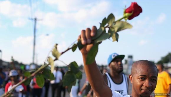 Un manifestante sostiene una rosa durante la marcha en Ferguson para pedir justicia por la muerte de Michael Brown.