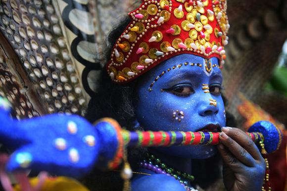 Un joven de Bangladesh está vestido como el Dios hindú Señor Krishna, donde participa en una procesión durante la celebración del festival de Janmashtami, el cual marca el nacimiento del Dios hindú. Foto: Munir Uz Zaman/AFP.