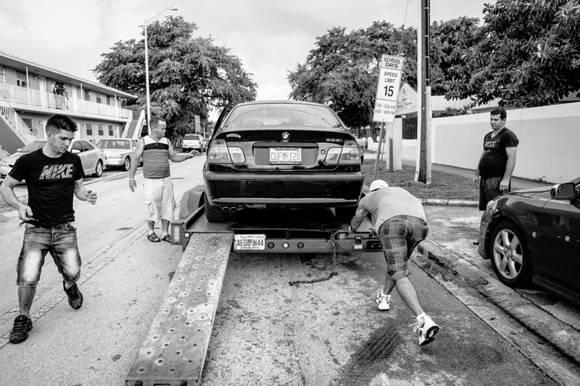 El carro deportivo rojo que compró Julio primero tuvo que ser reparado, y para ello contó con la ayuda de varios cubanos de Hialeah. Foto: Fulvio Bugani