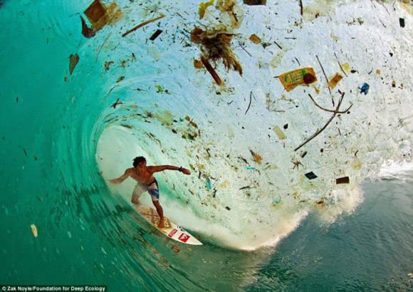 La persona que practica surf de Indonesia Dede Surinaya cabalga una ola de suciedad y basura (Java, Indonesia).