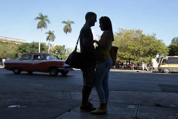 Una pareja de jóvenes, en actitud cariñosa mientras aguarda la llegada de un bus en el municipio de Centro Habana, en la capital de Cuba. Entre varones jóvenes crece la moda de la peligrosa implantación casera de una llamada perla, por creer que mejora las relaciones sexuales. Crédito: Jorge Luis Baños/ IPS.