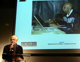 El exiliado Eduardo Manet muestra una imagen del periodista independiente Guillermo Fariñas, premiado por RSF, en Paris el 12 de diciembre de 2006.