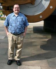 Nate Edel, in London 2005, standing in front of a battleship cannon
