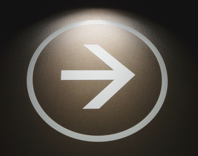 white arrow signage on black wall