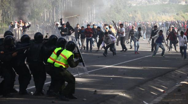Police dodge rocks and sticks in El Chasqui, south of Quito, as they clear the Pan American Highway.