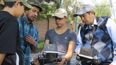 An instructor in Mexico City shows students how to operate drone controls.
