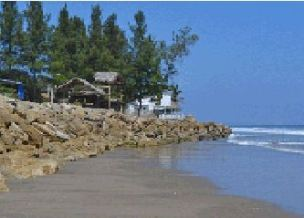 Only rocks and sand bags keep the ocean out of this house in Santa Elena Province.