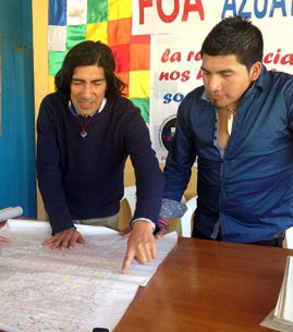 Mining opponent Carlos Perez, left, looks at a map of the Rio Blanco region west of Cuenca.
