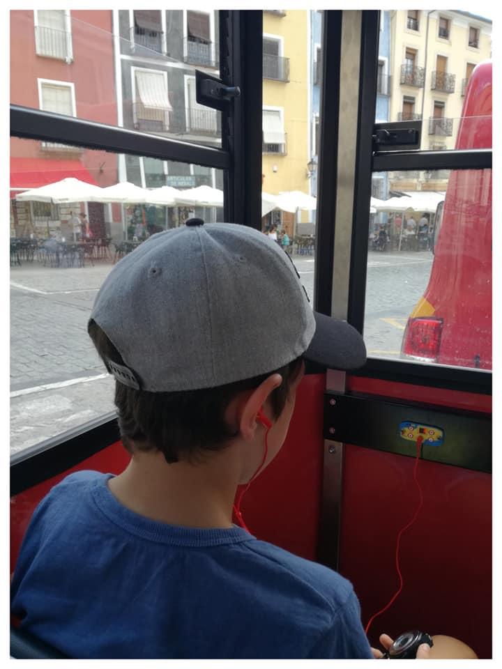 Mi mayor, con los cascos puestos, listo para no perderse nada del viaje en el tren turístico por Cuenca