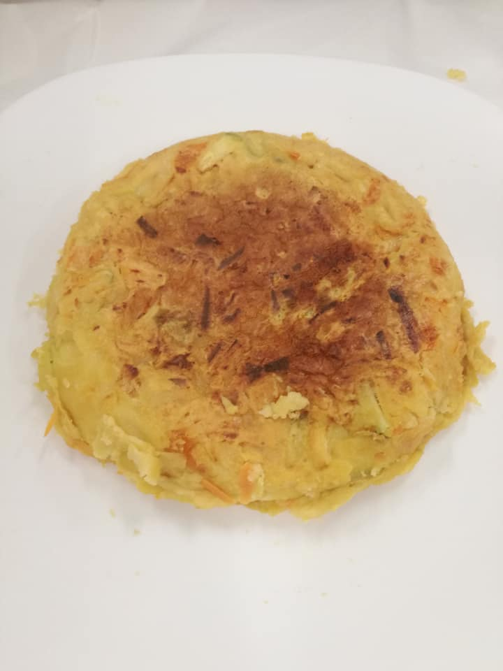Tortilla vegana hecha con harina de garbanzos y verduras en crudo