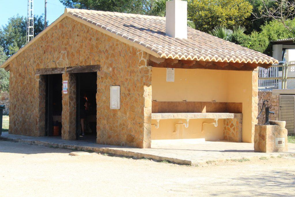 La casa con las barbacoas en el interior y los lavabos en el exterior. Al otro lado están los aseos