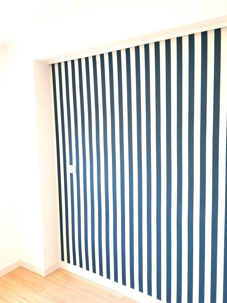 Papel pintado de rayas azul marino y blancas que llama la atención nada más entrar en la habitación de mi hijo