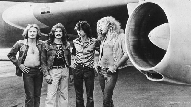 Led Zeppelin members posing in front of a plane. Photo by Julio Zeppelin
