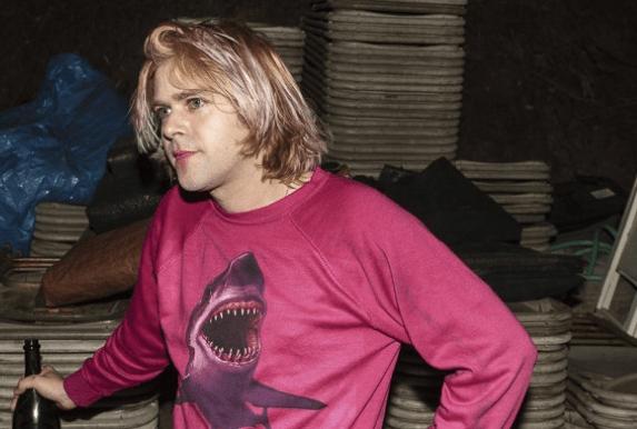 A teddy bear in a shark sweatshirt