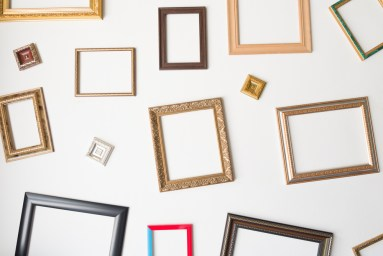 A white wall bears many different blank art frames.