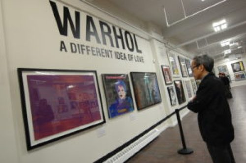 A photo of a man looking at Andy Warhol paintings.