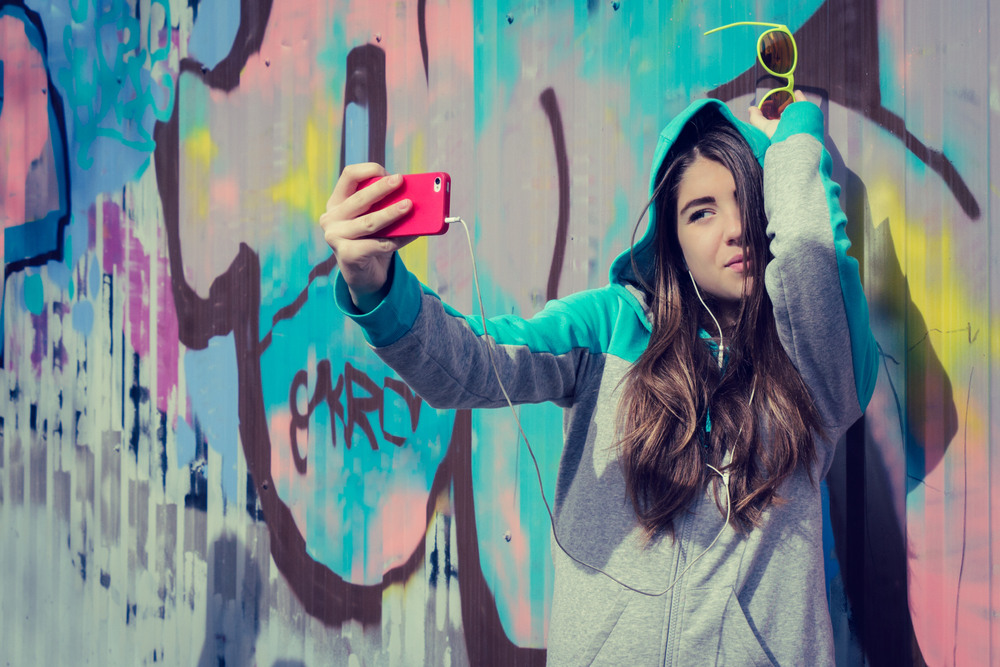 A young woman taking a selfie in front of a street art mural.
