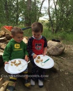 Little boys eating campfire baked apple crisp and hand whipped cream.