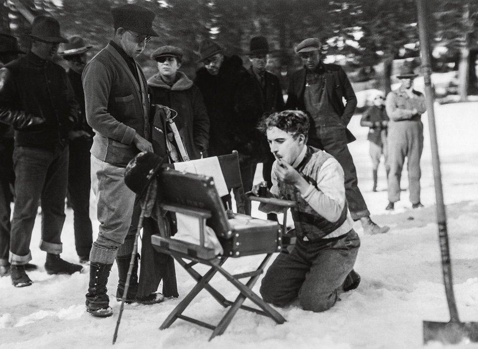 Chaplin alle prese con il trucco di scena durante le riprese del film La febbre dell'oro (1925). © Roy Export Company Establishment.