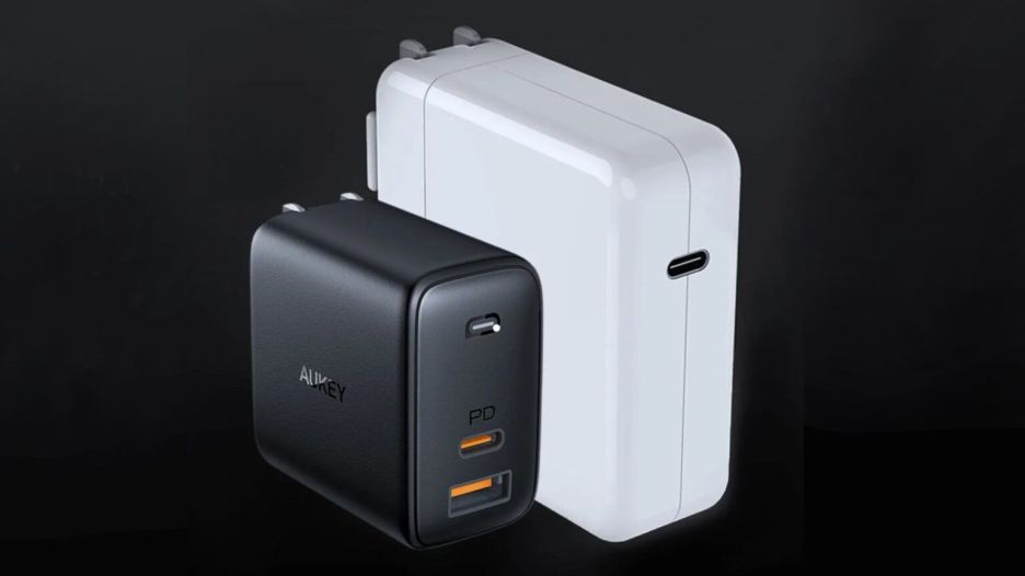 A bulky Apple charger next to a svelte Aukey one.
