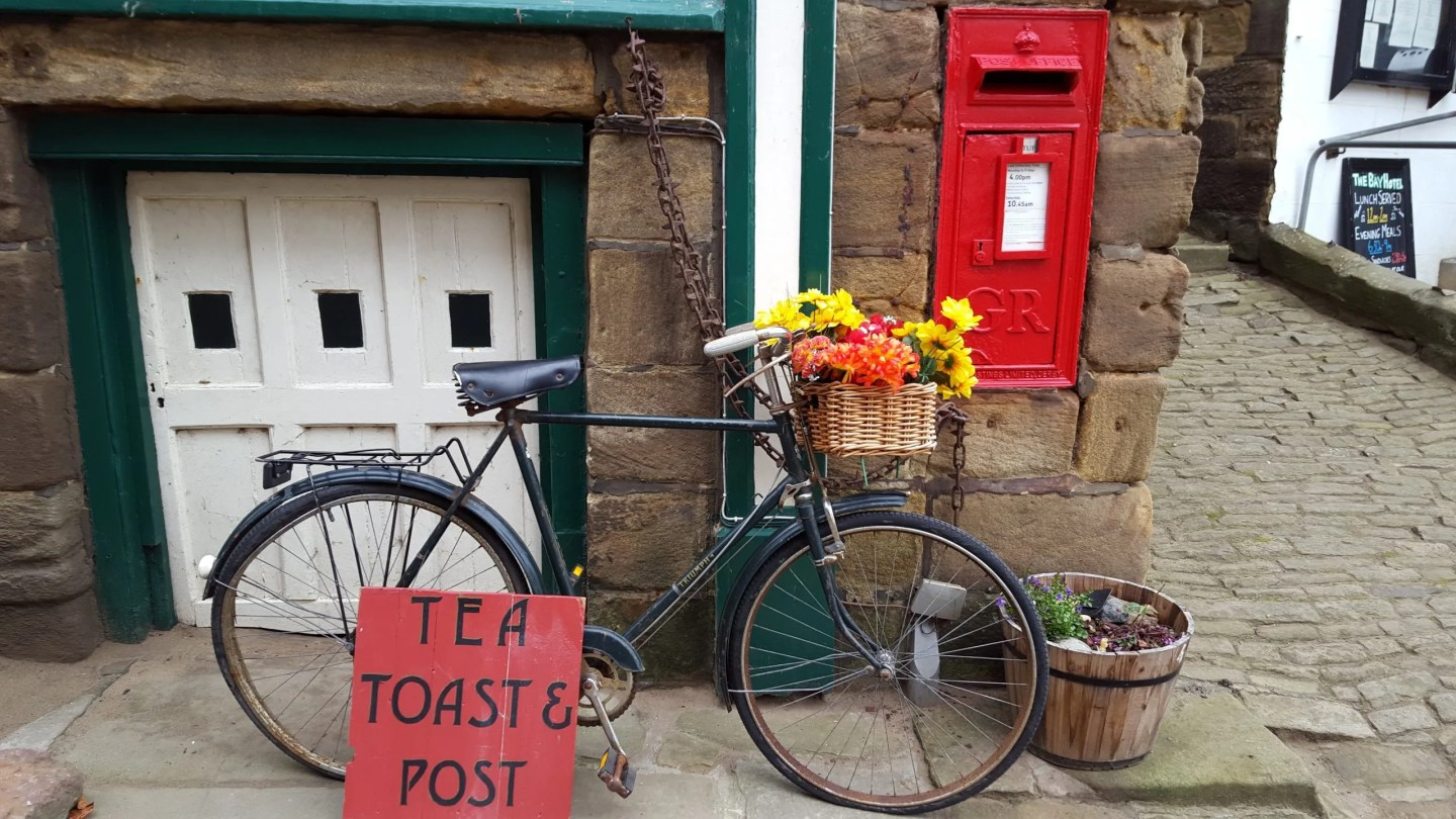 Bicycle with flowers in basket by red post box