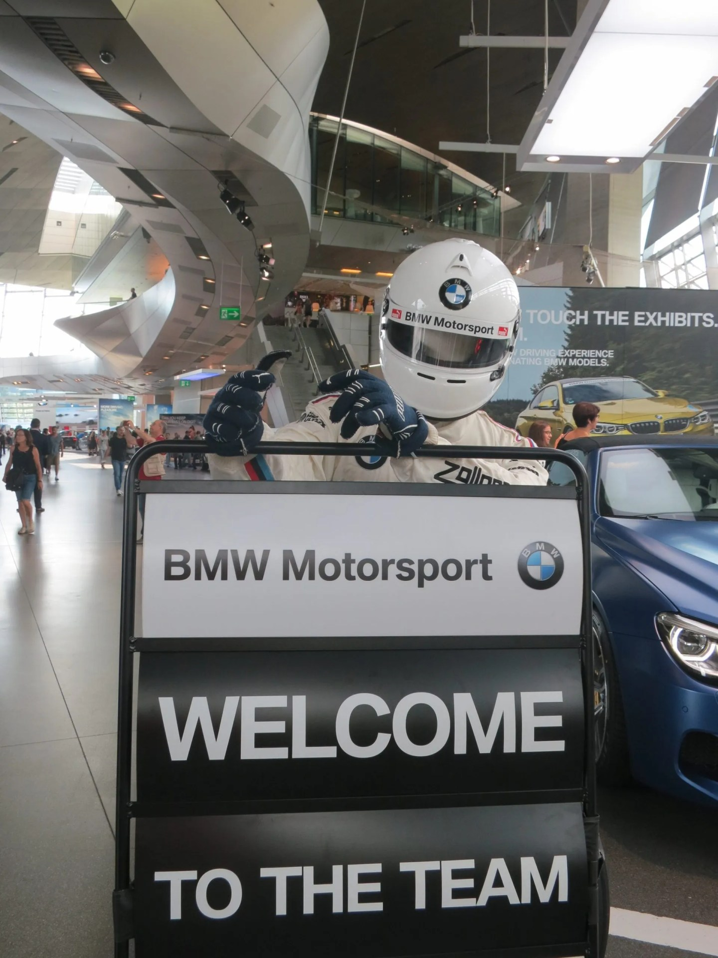 White helmeted racing driver welcome to BMW World and Museum