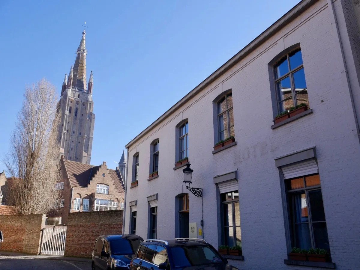 Exterior Bonobo Apartments Bruges with church tower behind