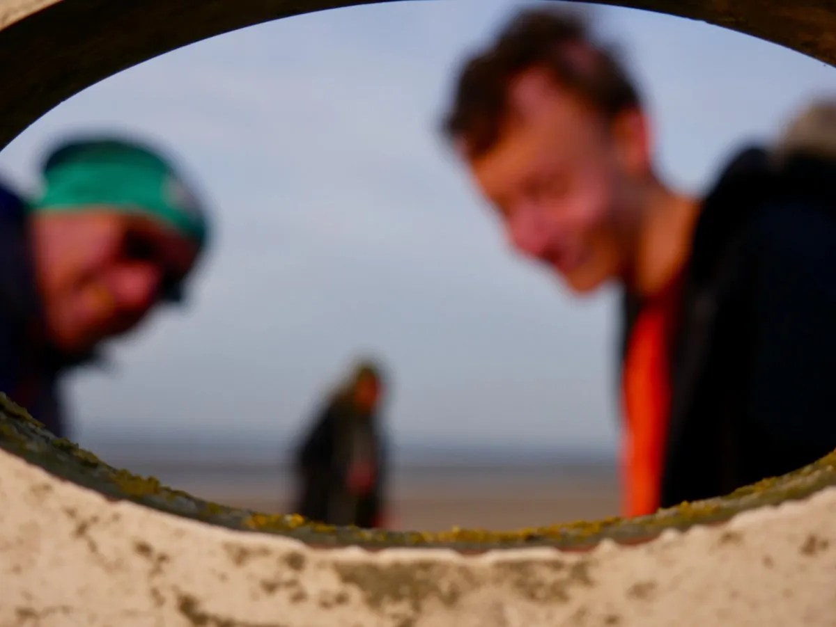 Blurry portrait three men looking though a port hole