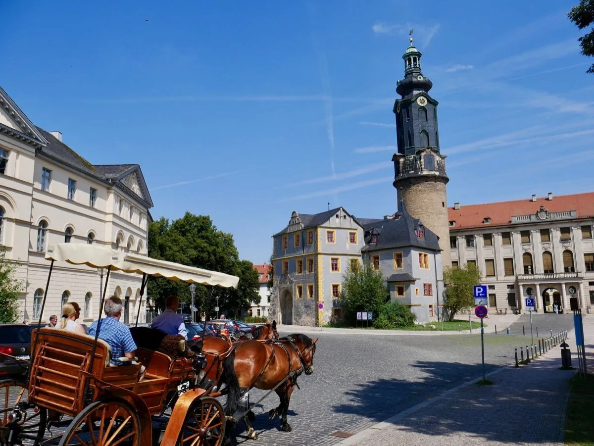 Horse drawn carriage drives past classical Weimar buildings