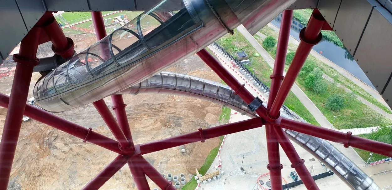 Sinuous steel tube slide descending through red steel rods at Orbit London